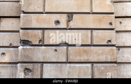 Old Bomb and Shrapnel Damage sustained during the Blitz on the walls of St. Bartholomews Hospital in London. - Stock Photo