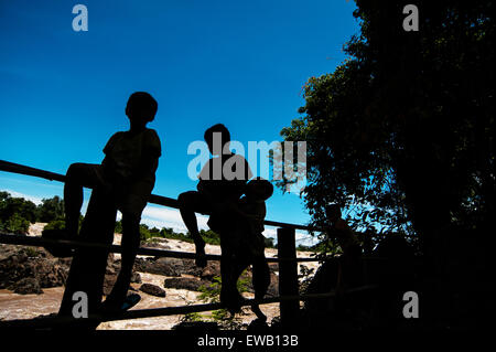 Little boy sitting on a fence at Khone Phapheng water fall or mekong river in champasak southern of laos one of - Stock Photo