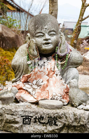 Japan, Miyajima. Daisho-in temple. Small Jizo statue of a sitting Buddhist monk in contemplation, with both hands - Stock Photo