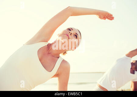 close up of couple making yoga exercises outdoors - Stock Photo