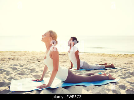 couple making yoga exercises outdoors - Stock Photo