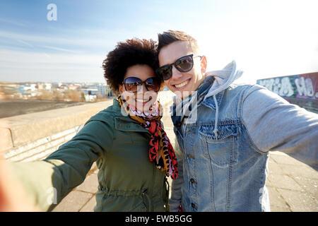 happy teenage couple taking selfie on city street - Stock Photo