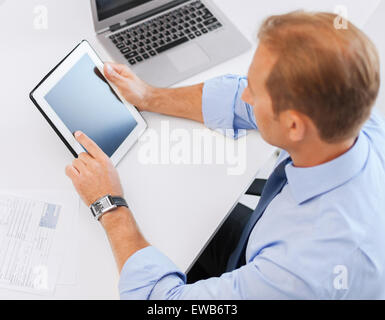 businessman with tablet pc and papers in office - Stock Photo