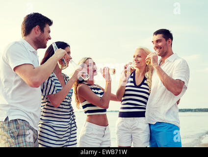smiling friends with drinks in bottles on beach - Stock Photo