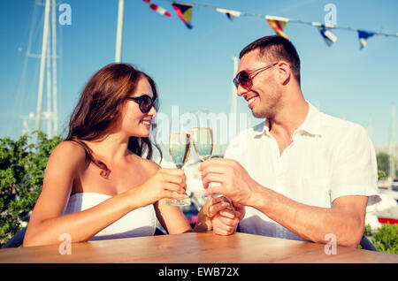smiling couple drinking champagne at cafe - Stock Photo