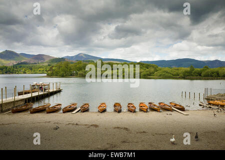 Series of owing boats lined up along the shore of lake Derwentwater - Stock Photo
