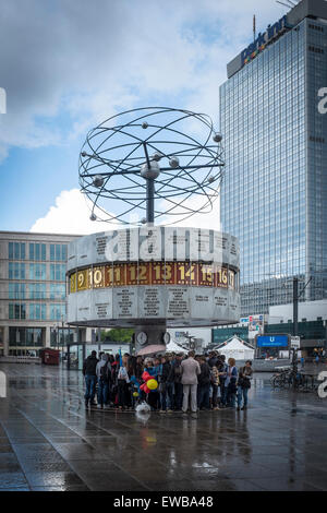 People under the World Time Clock, Berlin, Germany - Stock Photo