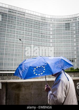 Brussels, Belgium. 22nd June, 2015. Pedestrian under umbrella with European Union flag is walking along European - Stock Photo