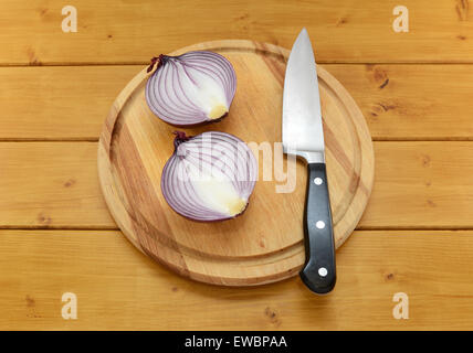Red onion cut in half with a sharp kitchen knife on a chopping board on a wooden table - Stock Photo