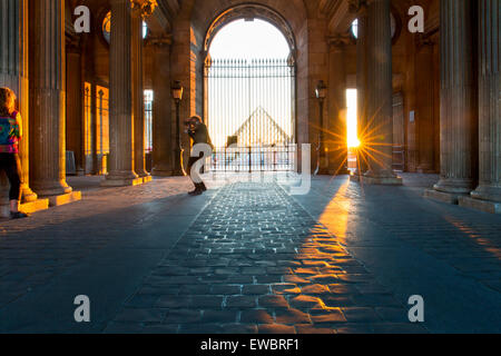 Photographer and model at gated entry to Musee du Louvre at sunset, Paris, France - Stock Photo