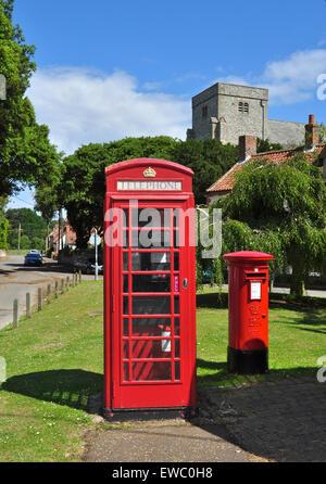 Telephone kiosk, post pillar box and church tower, Thornham, Norfolk, England, UK - Stock Photo