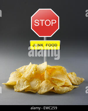 Junk food concept - potato chips and road stop sign - Stock Photo