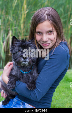 Caucasian teenage girl carrying and hugging black dog on arm in nature - Stock Photo