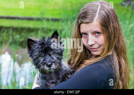 Blonde caucasian teenage girl carrying black dog on arm in green park - Stock Photo