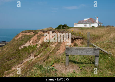 Sunny summer day with blue sky, Thornwick Bay, Yorkshire coast, GB, UK - view of crumbling cliffs, sea & wooden - Stock Photo