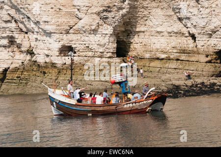 People on holiday set off on a sunny, summer day, sea boat trip, passing chalk cliffs - North Landing, Flamborough, - Stock Photo