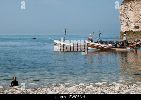 Blue sky on sunny summer day, passengers on 2 small boats ready for a sea trip, watched by girl on beach - North - Stock Photo