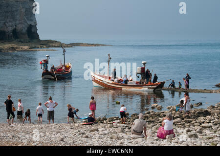 Blue sky on sunny summer day, passengers in 2 small boats ready for sea trip, watched by people on beach - North - Stock Photo