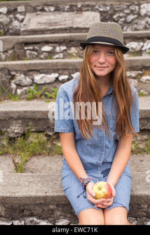 Teenage girl hipster in a hat and an apple in his hands, outdoors. - Stock Photo