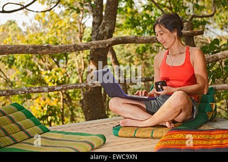 Woman sitting with her laptop on an outdoor terrase at a street cafe in northern Thailand - Stock Photo