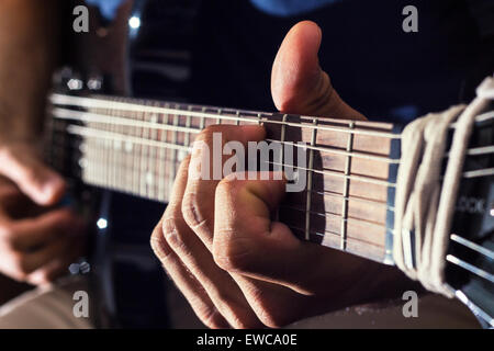 man plays guitar with his special talent under the flashlight - Stock Photo