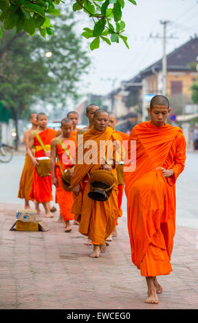 Monks during the alms giving ceremony in Luang Prabang, Laos. - Stock Photo