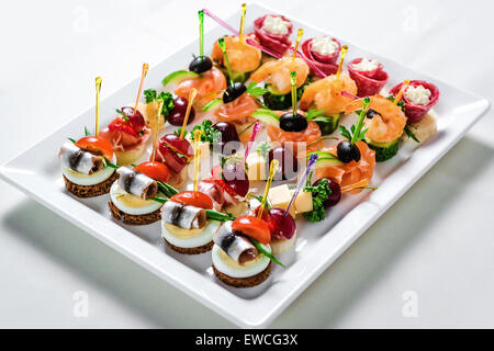 Plate with various seafood and meat canapes - Stock Photo