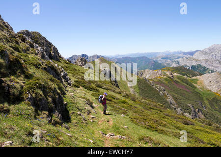 Hiker on the Mountain of Pico Loto with the View Towards Pico Hato and Beyond Across the Picos de Europa Mountains - Stock Photo