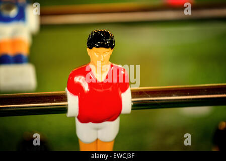 Single Player in Red Jersey, Vintage Foosball, Table Soccer or Football Kicker Game, Selective Focus, Retro Tone - Stock Photo