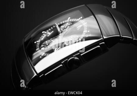Luxury mens chronograph watch made of black high-tech ceramics on black background. Closeup studio photo with selective - Stock Photo