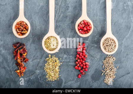 Various spices on black background with wooden spoons - Stock Photo