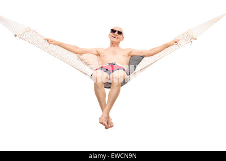Relaxed senior man in red swim trunks lying on a comfortable hammock isolated on white background - Stock Photo