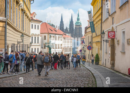 Prague Hradcany, along Uvoz in the Hradcany district of Prague a group of tourists head for the landmark St. Vitus - Stock Photo