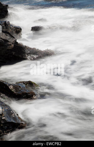waves crashing on the rocks with silky water - Stock Photo