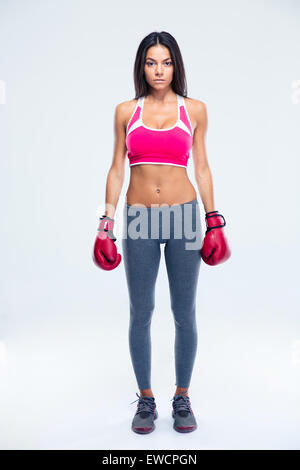 Serious fitness woman in boxing gloves standing over gray background. Looking at camera - Stock Photo