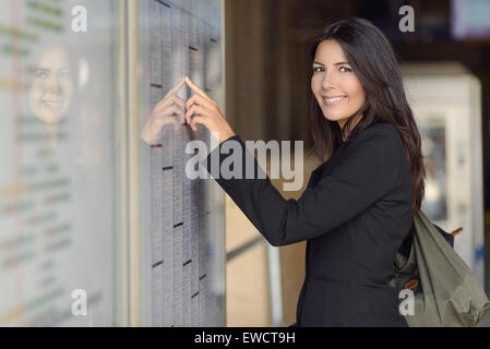 Attractive woman reading the train timetable running down the columns with her finger looking at the camera with - Stock Photo