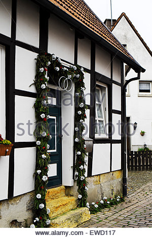An old post-and-beam house in Tecklenburg, Germany, has a wreath of silver-colored roses commemorating a 25th Anniversary. - Stock Photo