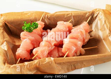 Raw chicken skewers on baking parchment paper - Stock Photo