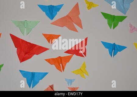 Paper butterflies on a white wall in the South of France - Stock Photo