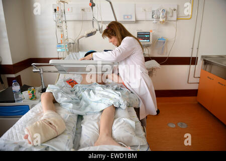 Doctor next to young patient's bed in pediatric hospital ward - Stock Photo
