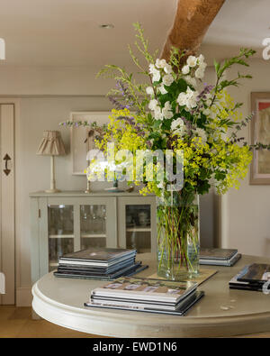 Vase of flowers on round console table - Stock Photo