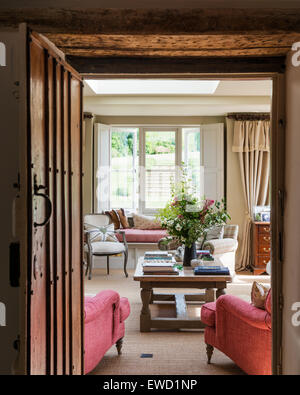 View through wooden doorway to sitting room with low coffee table and red armchairs - Stock Photo