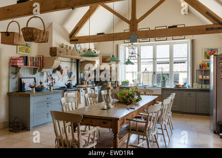 Vintage farmhouse table in rustic kitchen with green pendant lights from Holloways of Ludlow, aga, and beamed ceiling - Stock Photo