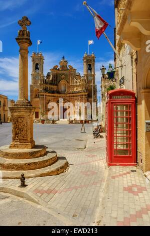Church of the Visitation and red telephone box Gharb, Gozo Malta - Stock Photo