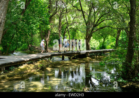 Tourists on boardwalk at Skradinski Buk waterfalls, Krka National Park on Dalmatian Coast of Croatia - Stock Photo