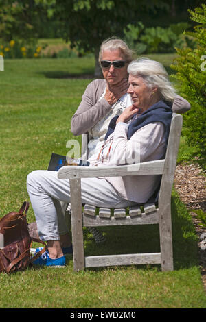 Two elderly women sitting on bench relaxed and enjoying the sunshine at Dorset in June - Stock Photo