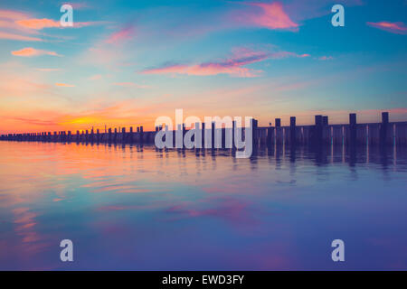 Beautiful ocean scene with wooden pier at sunset - Stock Photo