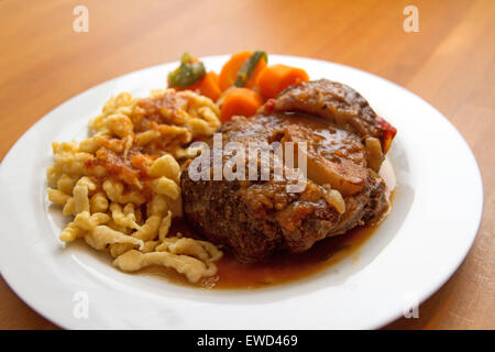 Ossobuco with spaetzle and carrots - Stock Photo