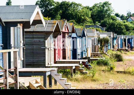 Row of wooden beach huts along Whitstable beach - Stock Photo