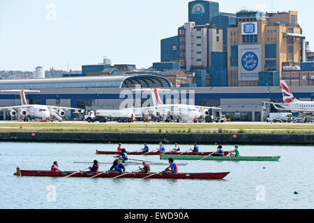 Airplane at London City Airport rowers training in old Royal Docks next to runway London Docklands Newham England - Stock Photo